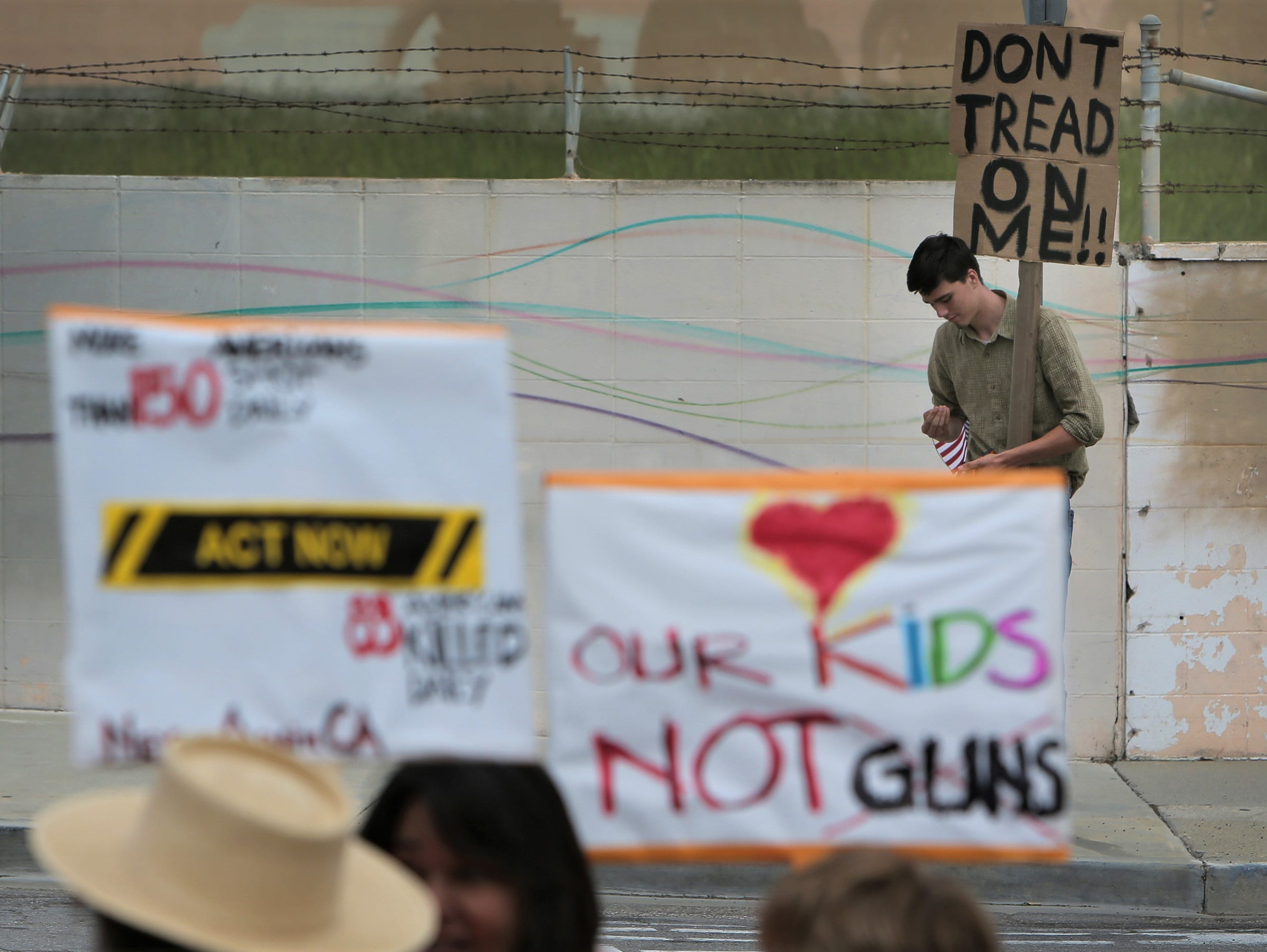 Foothill High School junior Collin McClain holds up his sign opposing the gun-control advocates who were protesting on Saturday at the Crossroads of the West Gun Show on the Ventura County Fairgrounds.
