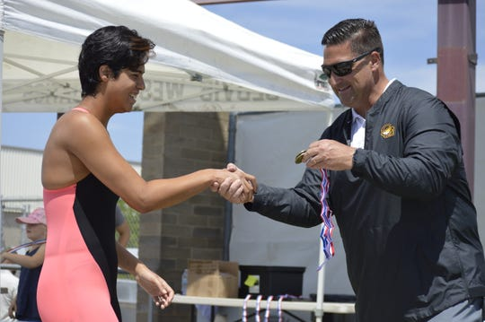 Golden West's Mackenzie Garza, left, is awarded the first-place medal after winning the girls 50-yard freestyle on Saturday at the Central Section swimming championships at Clovis West High School.