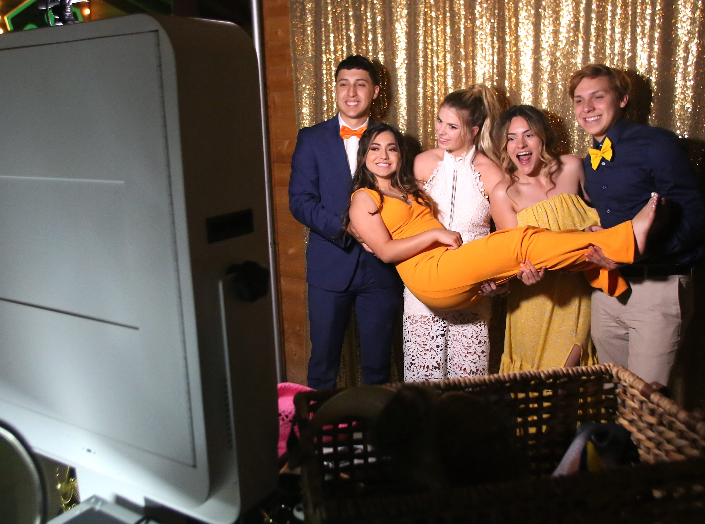 Jonathon Guerra, Mackenzie Williams, Shady Gonzales and Bryce Buchanan hold up Aliyah Alvarez in the photo booth at this year's Exeter Union High School prom Saturday, May 4, 2019 in Woodlake, Calif.