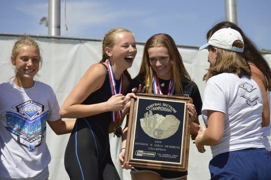 The Golden West High School girls swim team celebrates after winning the Central Section Division II team title on Saturday at Clovis West High School.