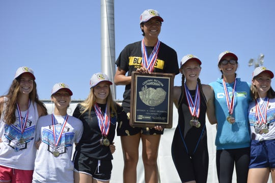 The Golden West High School girls swim team stands atop the podium after winning the Central Section Division II team title on Saturday at Clovis West High School.