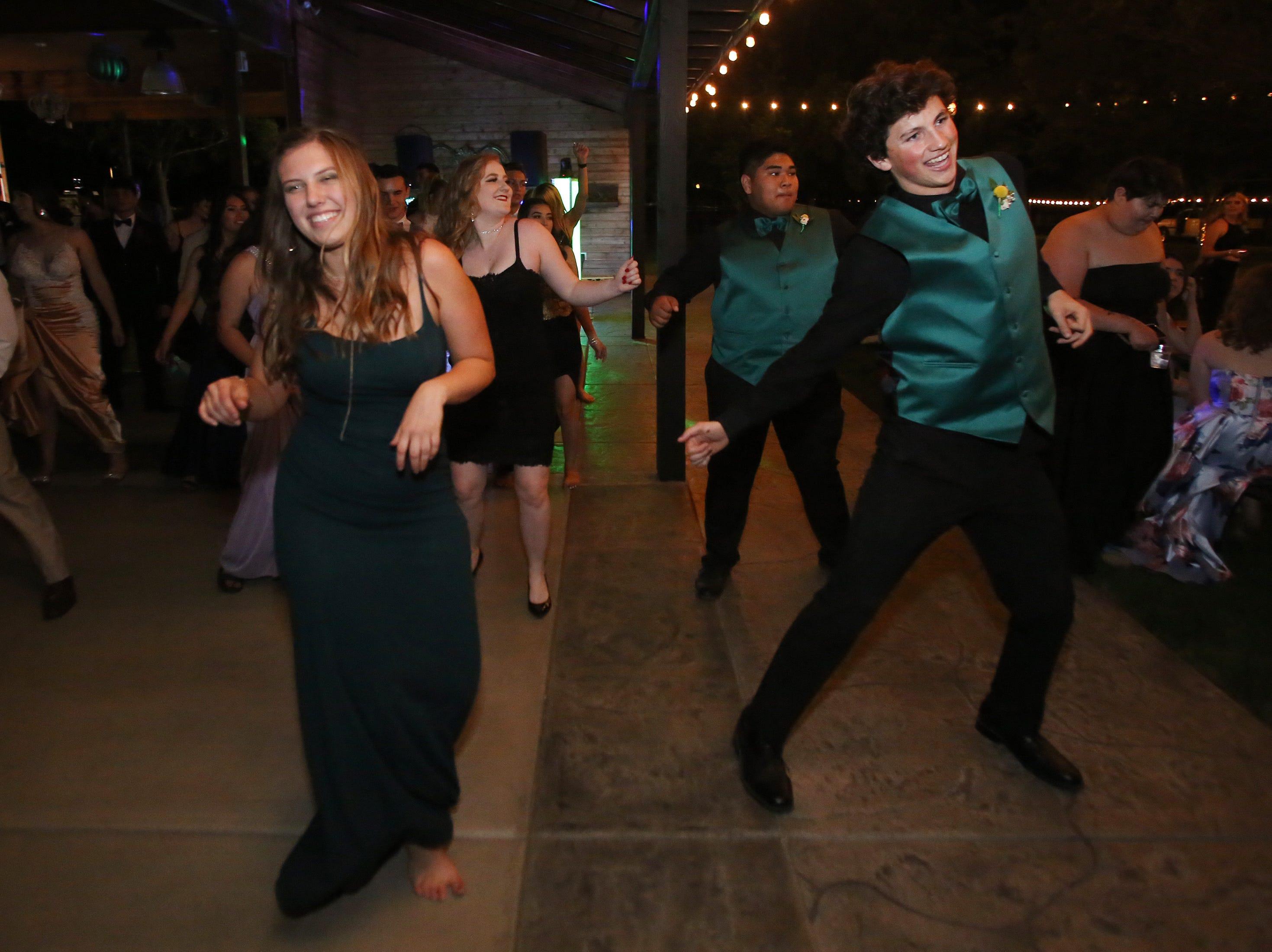Morgan Weldon, left and Caleb Peltzer enjoys the dance festivities as Morgan Dougherty and Nicholas Tangonan behind dance along at the Exeter Union High School prom Saturday, May 4, 2019 in Woodlake, Calif.