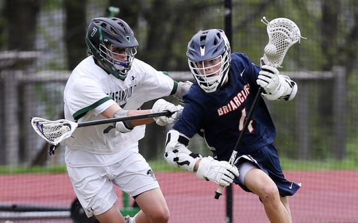 Briarcliff's Jack Ricardi (4) tries to get around Pleasantville's Erik Roye (7) during boys lacrosse action at  Pleasantville High School May 4, 2019. Briacliff won the game 9-8.