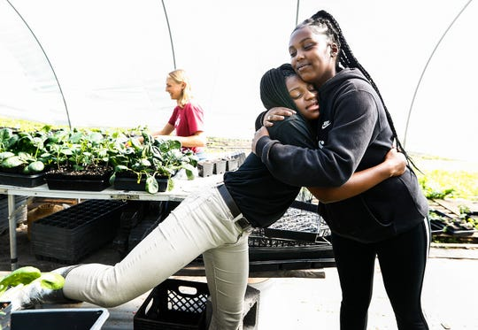 Tamia Coleman, 16, left, hugs Girls Inc. Youth Farm program manager Kenya Ghanor while working in the farm's greenhouse in Friday, April 26, 2019 in Memphis, Tenn. Girls harvest every Friday; for produce sold every Saturday at the Farmers Market.