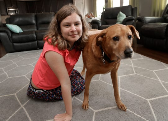 Sobie Cummings, 11, plays with her dog, Dallas, at the family's home in Waxhaw, N.C., Friday, March 29, 2019. A psychiatrist suggested that a service dog might help to ease Sobie's crippling anxiety and feelings of isolation. But when they brought home a $14,500 Briard from Mark Mathis' Ry-Con Service Dogs, Okami broke from Glenn Cummings' grasp and began mauling Dallas. (AP Photo/Chuck Burton) ORG XMIT: NY426