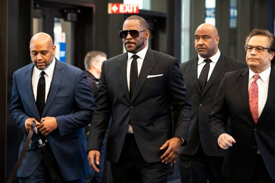 R. Kelly walks with attorneys and supporters into the Leighton Criminal Courthouse in Chicago on March 22, 2019.