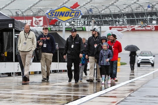 NASCAR fans walk on pit road whle rain falls at Dover International Speedway on Sunday.