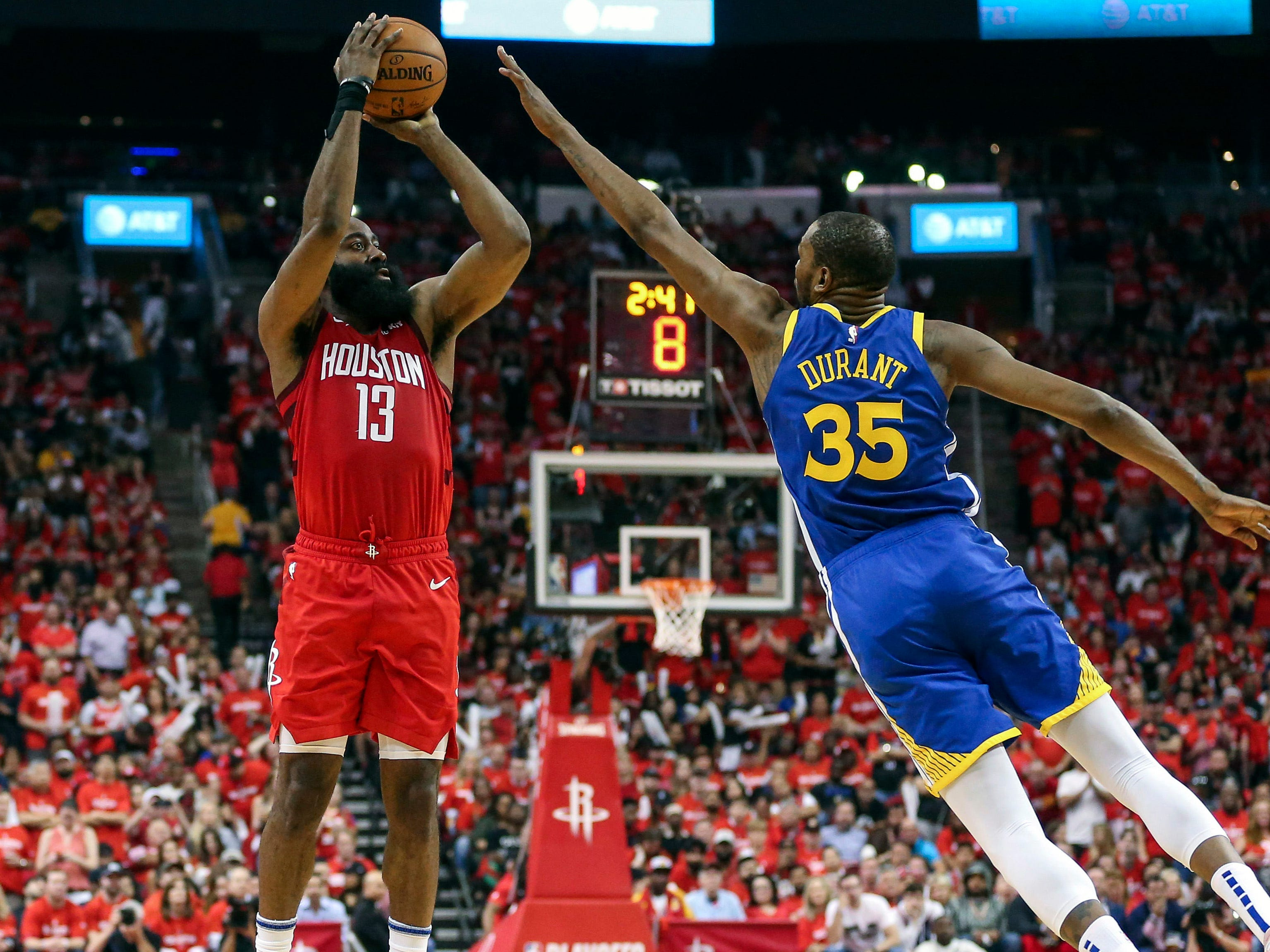 May 4: Rockets guard James Harden (13) shoots over the out-stretched hand of Warriors defender Kevin Durant (35) during Game 3 in Hosuton.