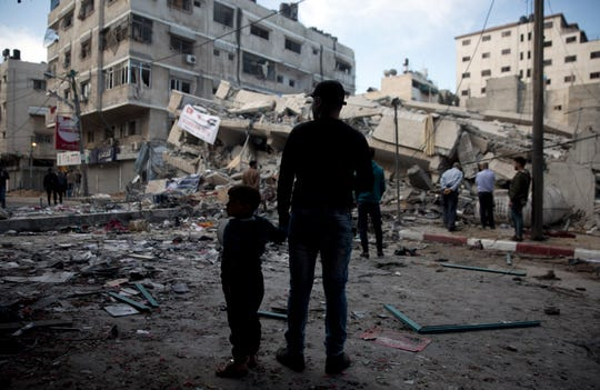 Palestinians stand in front of a destroyed multi-story building was hit by Israeli airstrikes late Saturday in Gaza City, Sunday, May 5, 2019.