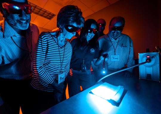 Lauren Regucci uses an alternate light source at Citizen's Academy, showing how biological evidence can fluoresce.