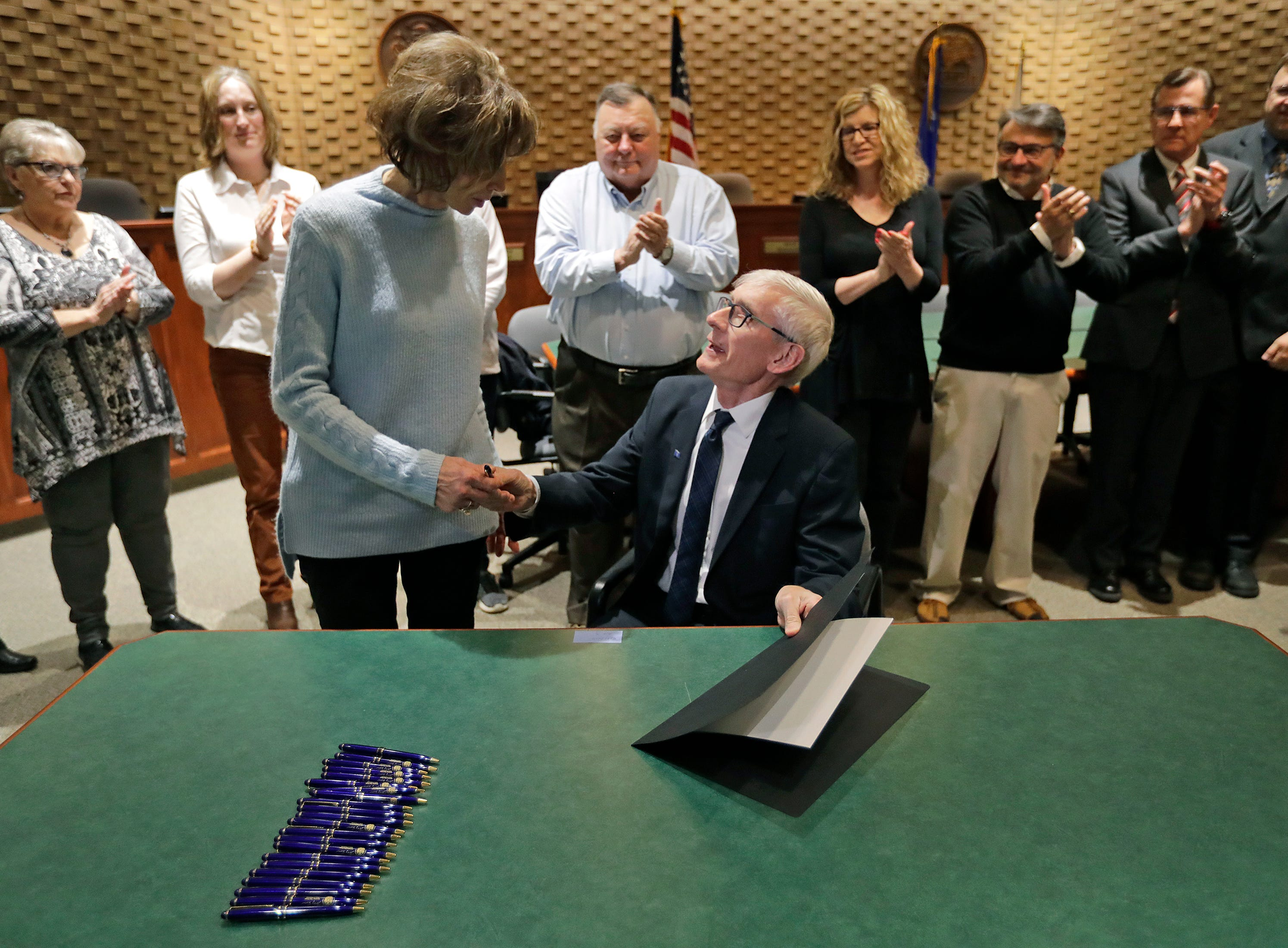 Gov. Tony Evers shakes hands with Sandy Ellis after he signs a bill naming the Interstate 41-U.S.10 interchange after the late Michael G. Ellis Wednesday, May 1, 2019, at Neenah City Hall in Neenah, Wis. Sandy is the widow of Michael G. Ellis. The two are surrounded by family members and officials.Dan Powers/USA TODAY NETWORK-Wisconsin