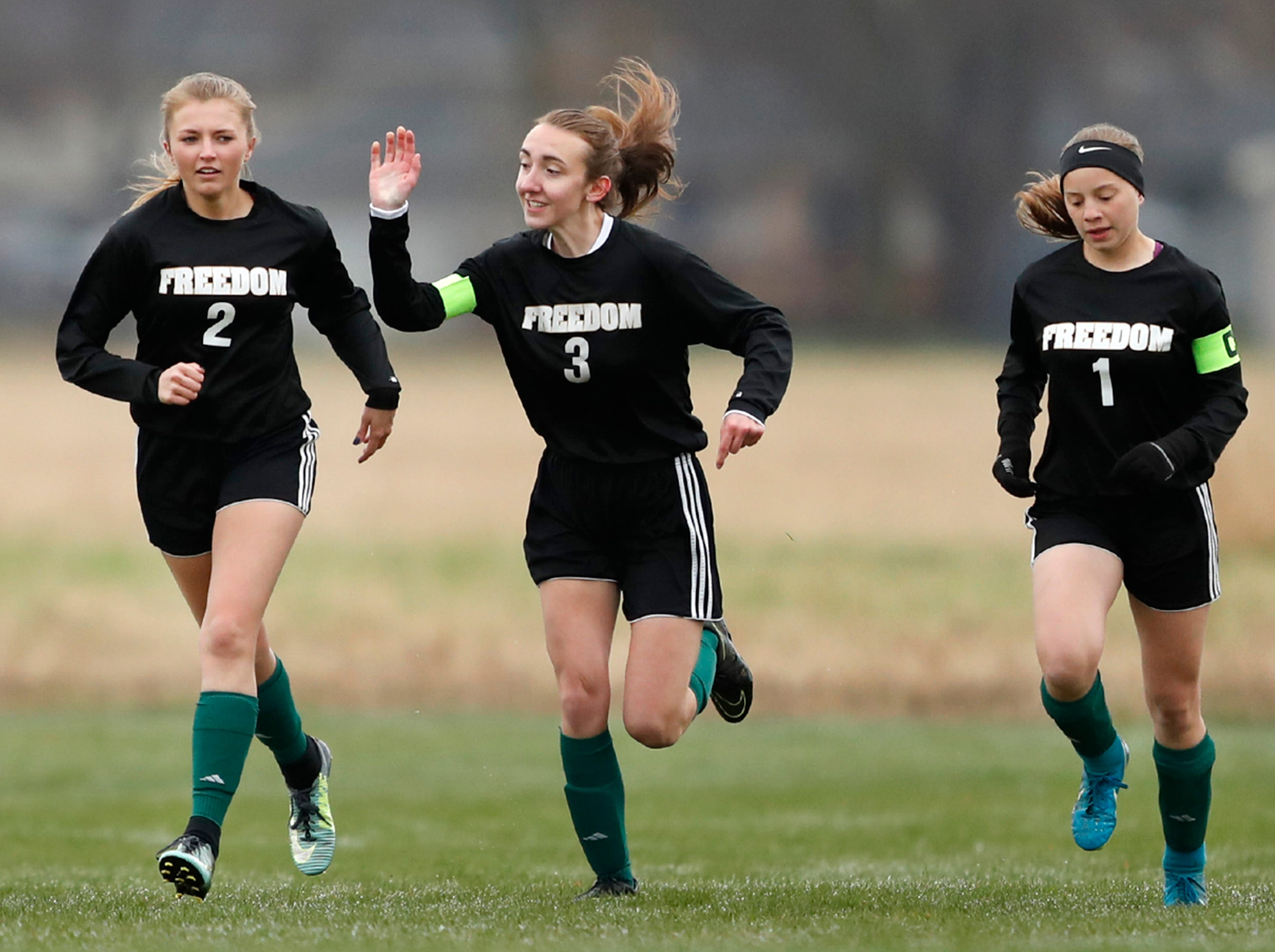 Freedom High School's Imigin Coenen (2) celebrates with teammates Sam Baumgartner (3) and Rosa Lezotte (1) after scoring the game's first goal against Waupaca High School Monday, April 29, 2019, in Freedom, Wis. Freedom won the game 11-0.Danny Damiani/USA TODAY NETWORK-Wisconsin