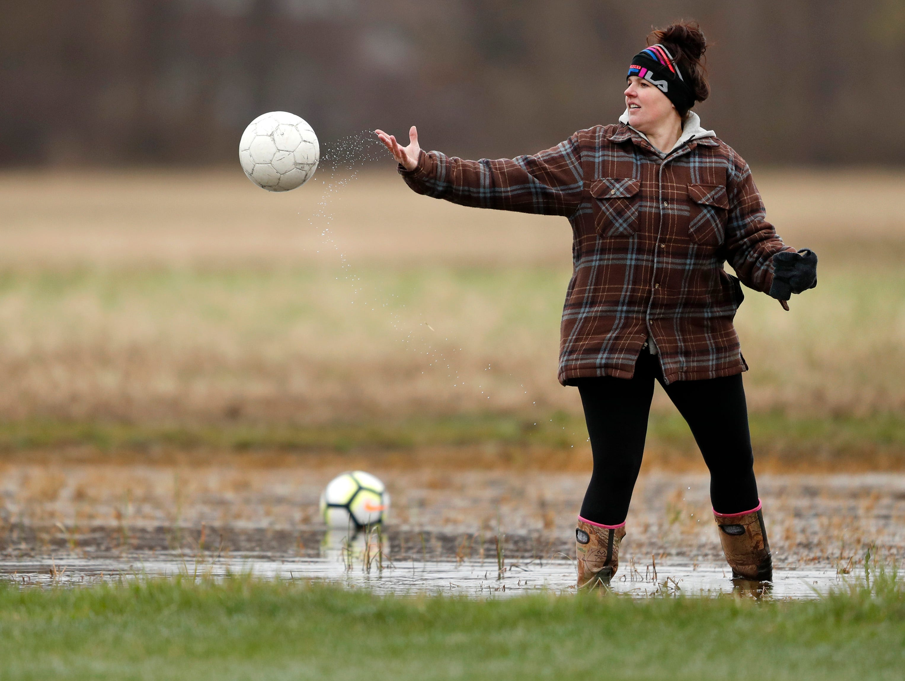 Desi Coenen, mother of Freedom midfielder Imigin Coenen, wades out into ankle deep water behind Waupaca High School's goal to collect game balls in the first half Monday, April 29, 2019, in Freedom, Wis. Danny Damiani/USA TODAY NETWORK-Wisconsin