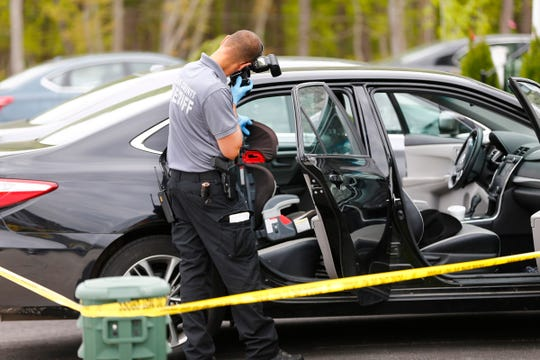 An Ocean County Sheriff's Department CSI officer photographs a car seat in the back seat of a car in a Lakewood driveway Monday afternoon.  A baby was allegedly found unresponsive in the car earlier and later died at the hospital.