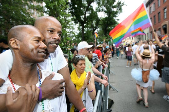 Ramon Flowers (left) and his boyfriend Rodney Lawrence watch the 2016 Pride Parade across from the Stonewall Inn in New York City.