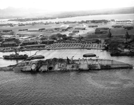 The USS Oklahoma rests on its side in Pearl Harbor as crews begin the process of righting the battleship. The Oklahoma never saw action again.