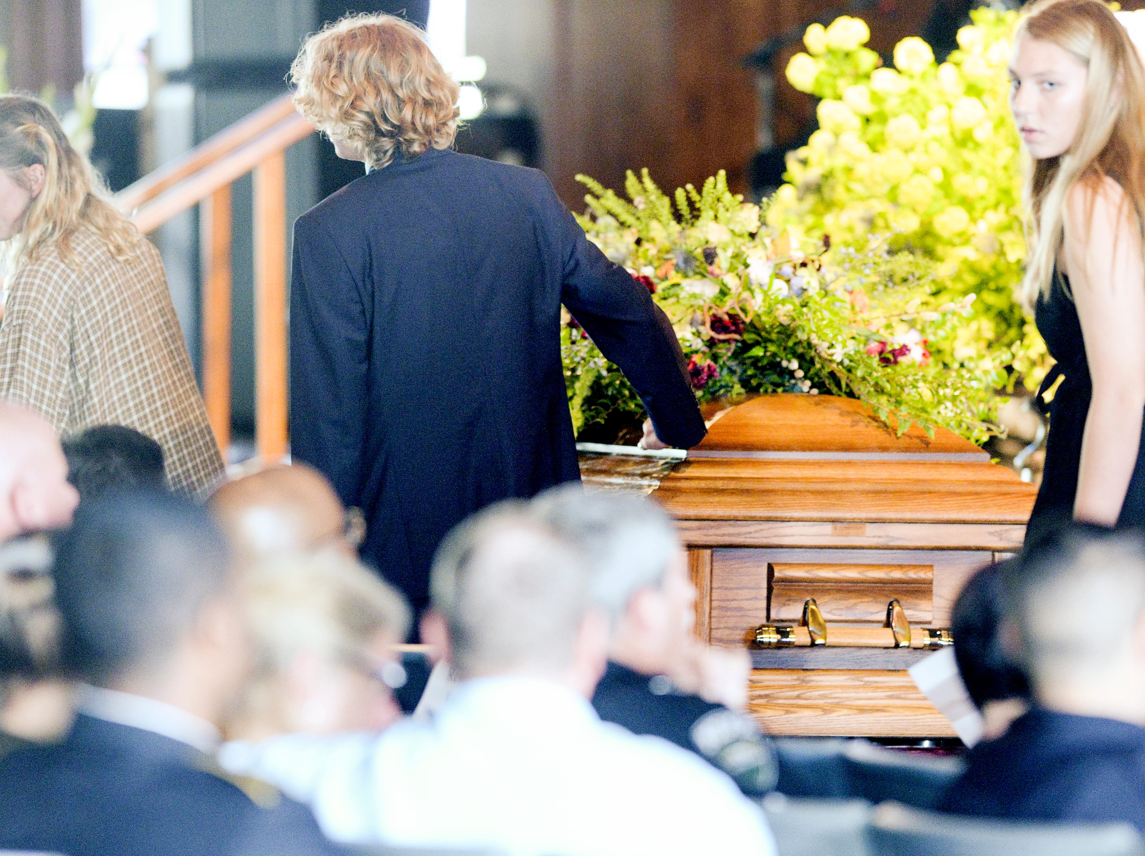 Riley Howell's brother, Teddy, 14, places a hand on his casket after speaking during a memorial service May 5, 2019, at Stuart Auditorium in Lake Junaluska, North Carolina.