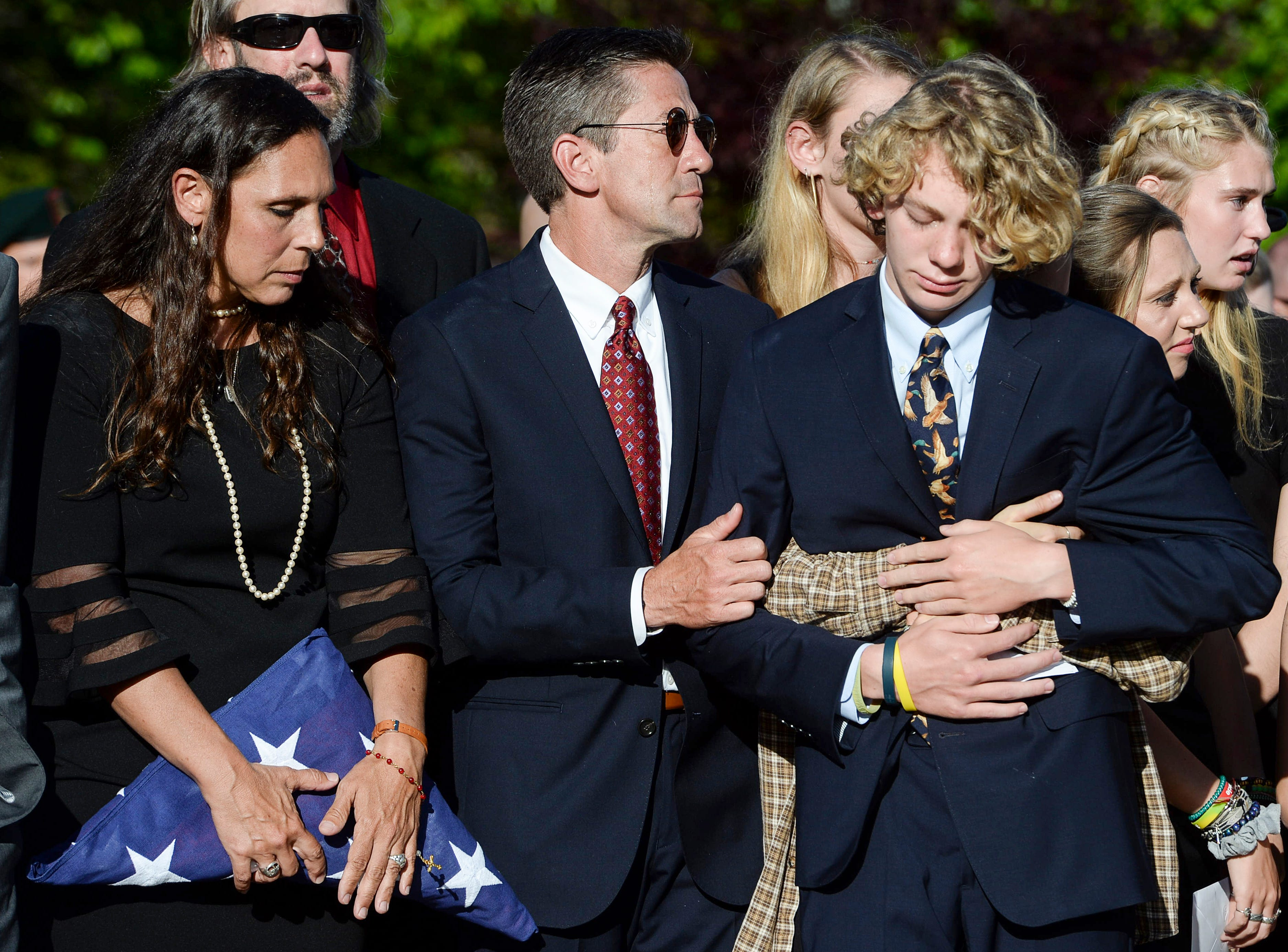Riley Howell's mother, Natalie Henry-Howell, and father, Thomas Howell, Jr., stand together as their son, Teddy, is hugged by Riley's girlfriend, Lauren Westmoreland, after acting as pallbearer following a memorial service for Riley in Lake Junaluska, North Carolina, May 5, 2019.