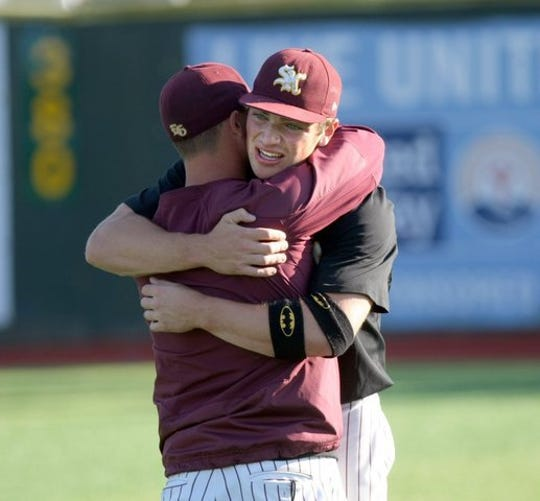 South Kitsap's Mac McCarty hugs head coach Marcus Logue after the Wolves won the Class 4A state baseball championship in 2015.