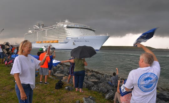 Marcia Slayton takes a photo of Steven Slayton of Cape Canaveal waving to the ship as it leaves port.  Royal Caribbean's Harmony of the Seas, then second largest cruise ship in the left just before 5 p.m. Monday.