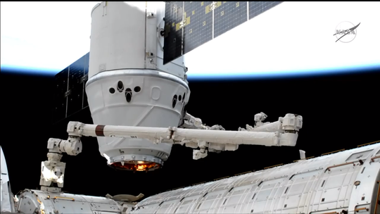 Astronauts pull SpaceX's Dragon spacecraft closer to the International Space Station using a robotic arm ahead of the capsule's installation Monday, May 6, 2019.