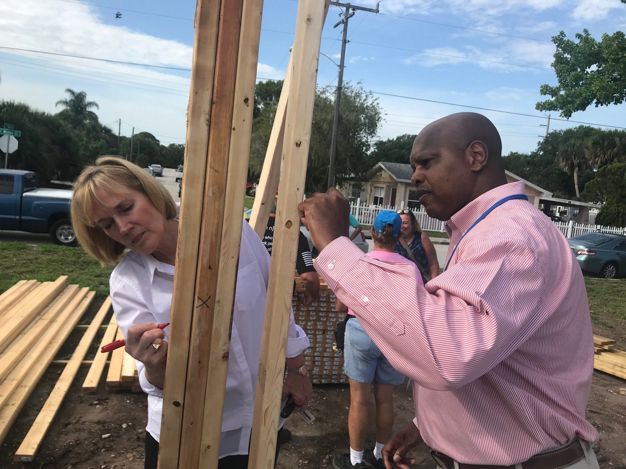 Delores Spearman, left, and Darryl Niles, sign the walls Monday at Karla Griggs' new home, which is being built by Habitat for Humanity of Brevard. Spearman and her husband Guy donated $100,000 check for the six-home project. Niles is program manager for the Community Redevelopment Agency of Cocoa.