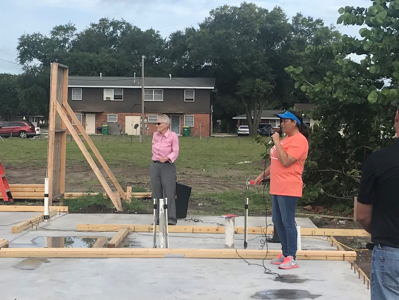 Habitat for Humanity of Brevard executive director Mary Kelly, right, listens Monday morning as Army veteran Karla Griggs talks with those gathered at the wall raising of her new home. Griggs' home is the first of six houses Habitat for Humanity of Brevard is building in Cocoa's Diamond Square neighborhood.