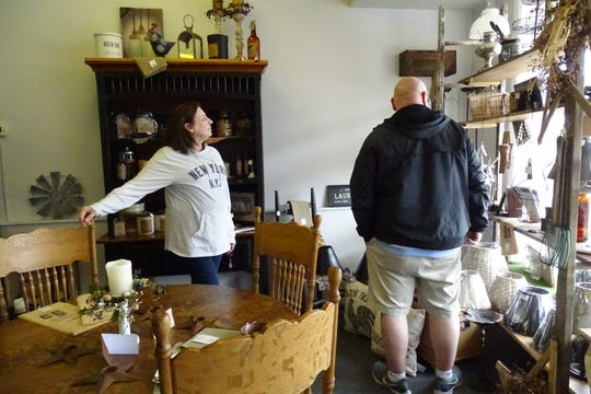 Debbie Schifer helps a customer at her newly opened shop, Annie's Primitive Marketplace, 238 S. Sandusky St.