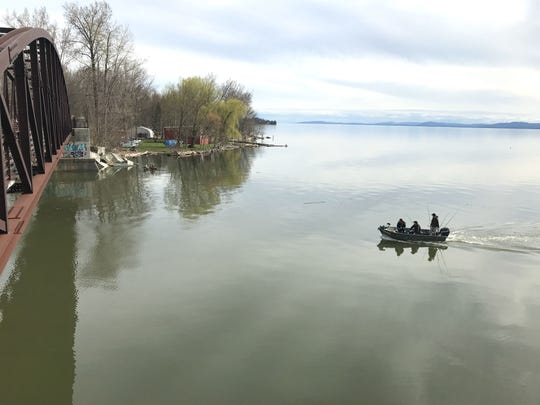 A fishing boat on Lake Champlain is about to pass under the bridge on the recreation path and enter the Winooski River on Sunday, May 5, 2019.