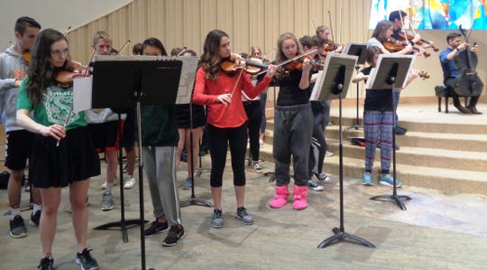 Loveland High School viola and violin players rehearse with band Break of Reality, creating a unique string-rock sound for a concert at Prince of Peace church.