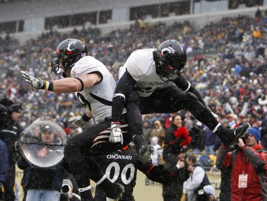 University of Cincinnati's Ben Guidugli, left, and Isaiah Pead bump booties after Pead's touchdown against the University of Pittsburgh during the fourth quarter of their game played at Heinz Field in Pittsburgh, Pennsylvania Saturday December 5, 2009. UC won 45-44.