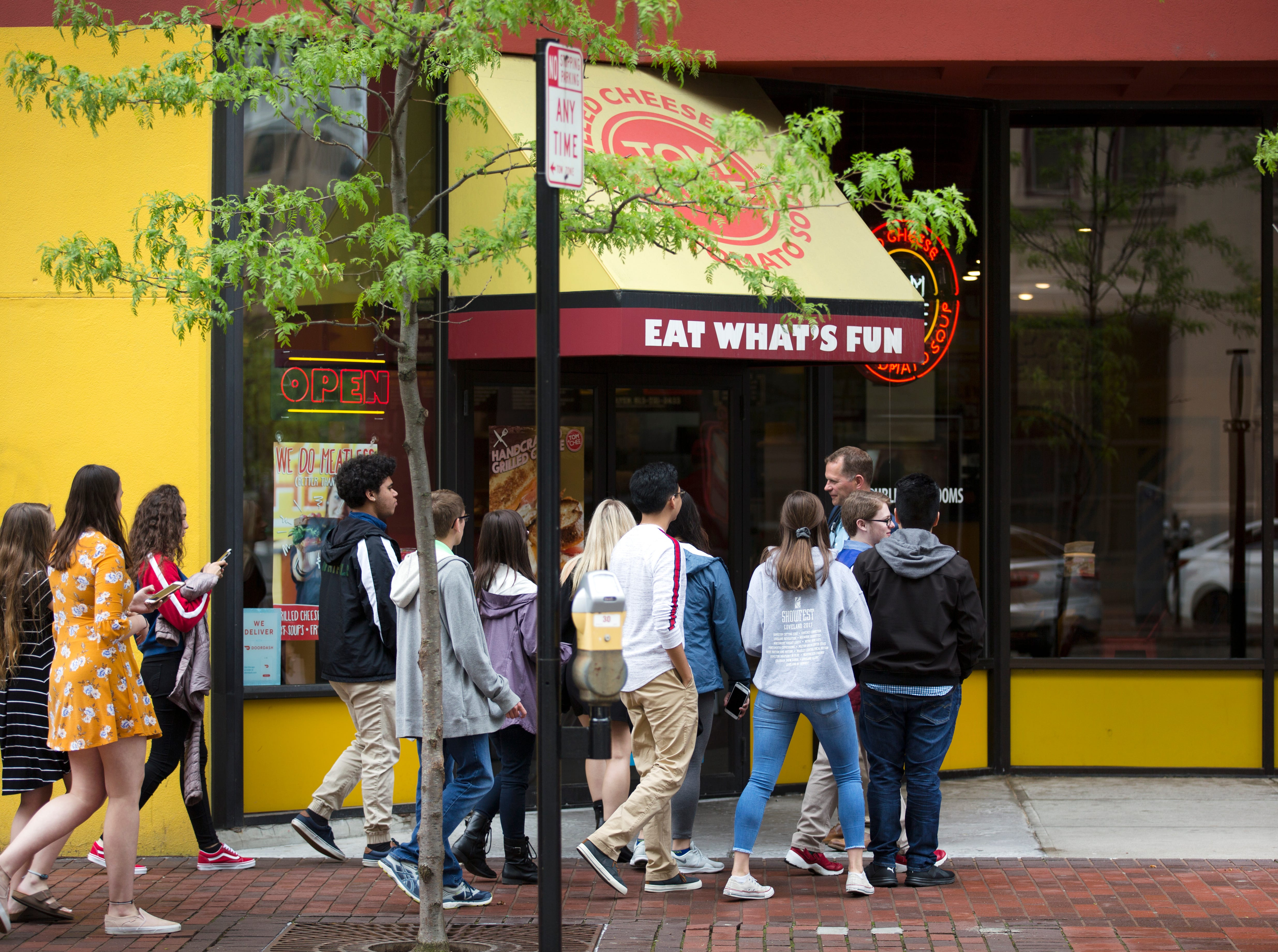A group of youths head into Tom + Chee on Court Street in downtown Cincinnati on Take Your Daughters and Sons to Work Day on Thursday, April 25, 2019. Tom + Chee begin in 2009 in a tent on Fountain Square. In 2017, Gold Star Chili acquired the unique restaurant, which is famous for it's grilled cheese donut. Just across the street The Kroger Co. is building a new 18-story mixed-use development that will include 139 apartments. The grocery portion will open in the fall. The 560-space garage is already open to the public. It seems fitting for Kroger to bring back the groceries to Court Street. The street started as the Canal Street Market back in 1829. The market operated between Vine and Walnut Streets. It lasted until 1915.