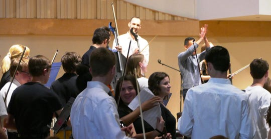 Loveland school orchestra students celebrate with Break of Reality band members following evening concert performance at a packed Prince of Peace Church.