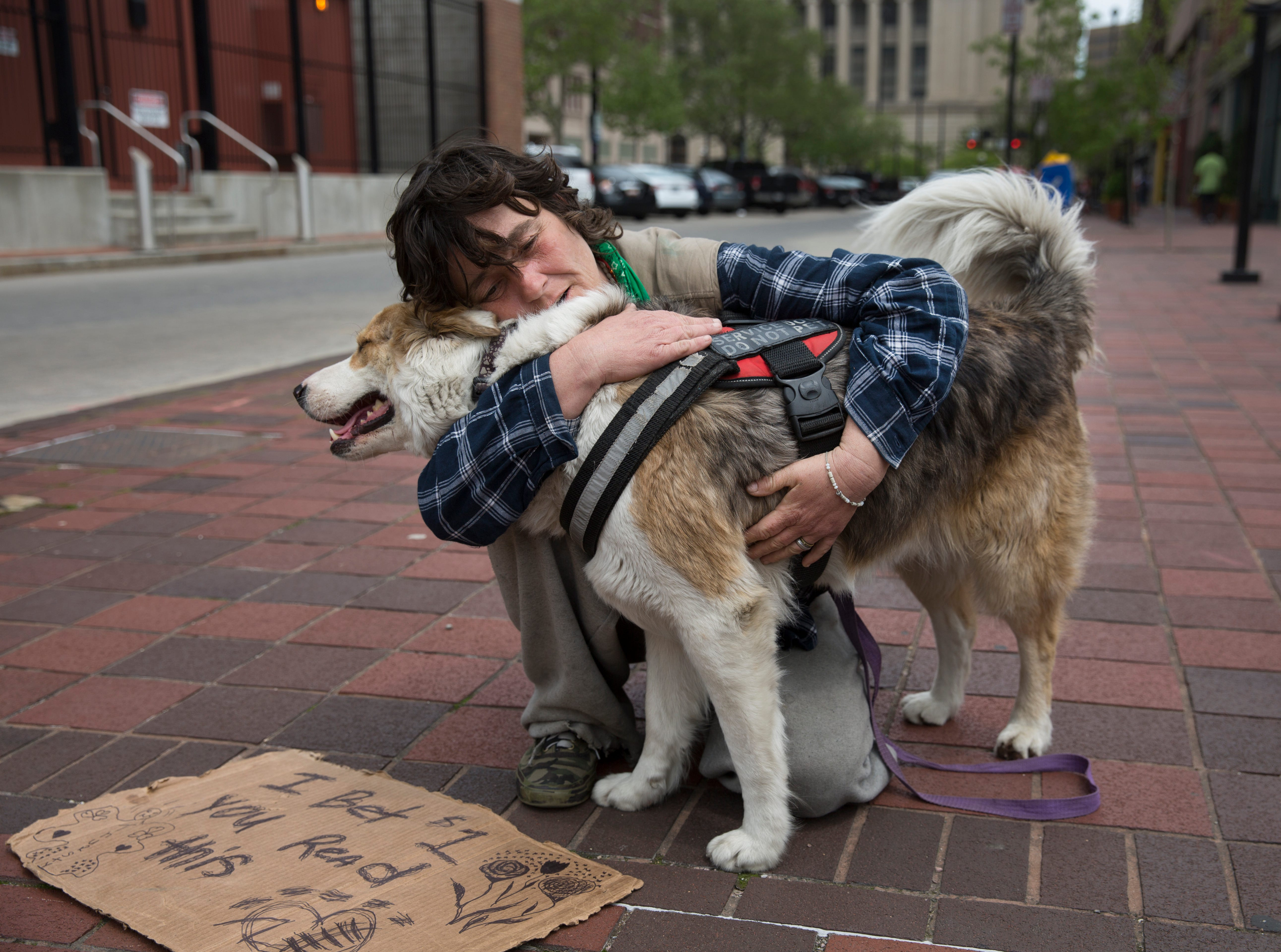 Katrina Wilson, 40, flies a sign on Court Street at Walnut, near the Hamilton County Courthouse, Wednesday, May 1, 2019. Wilson, who is homeless, keeps her six-year-old dog, Thirsty, with her. She said he's a service dog. Wilson is proud to say she's been sober off heroin for 12 months and counting.