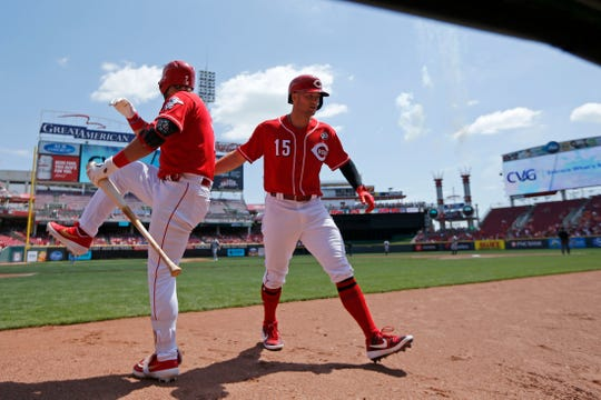 Cincinnati Reds center fielder Nick Senzel (15)  high fives with third baseman Eugenio Suarez (7) after hitting a solo home run in the first inning of the MLB National League game between the Cincinnati Reds and the San Francisco Giants at Great American Ball Park in downtown Cincinnati on Monday, May 6, 2019.