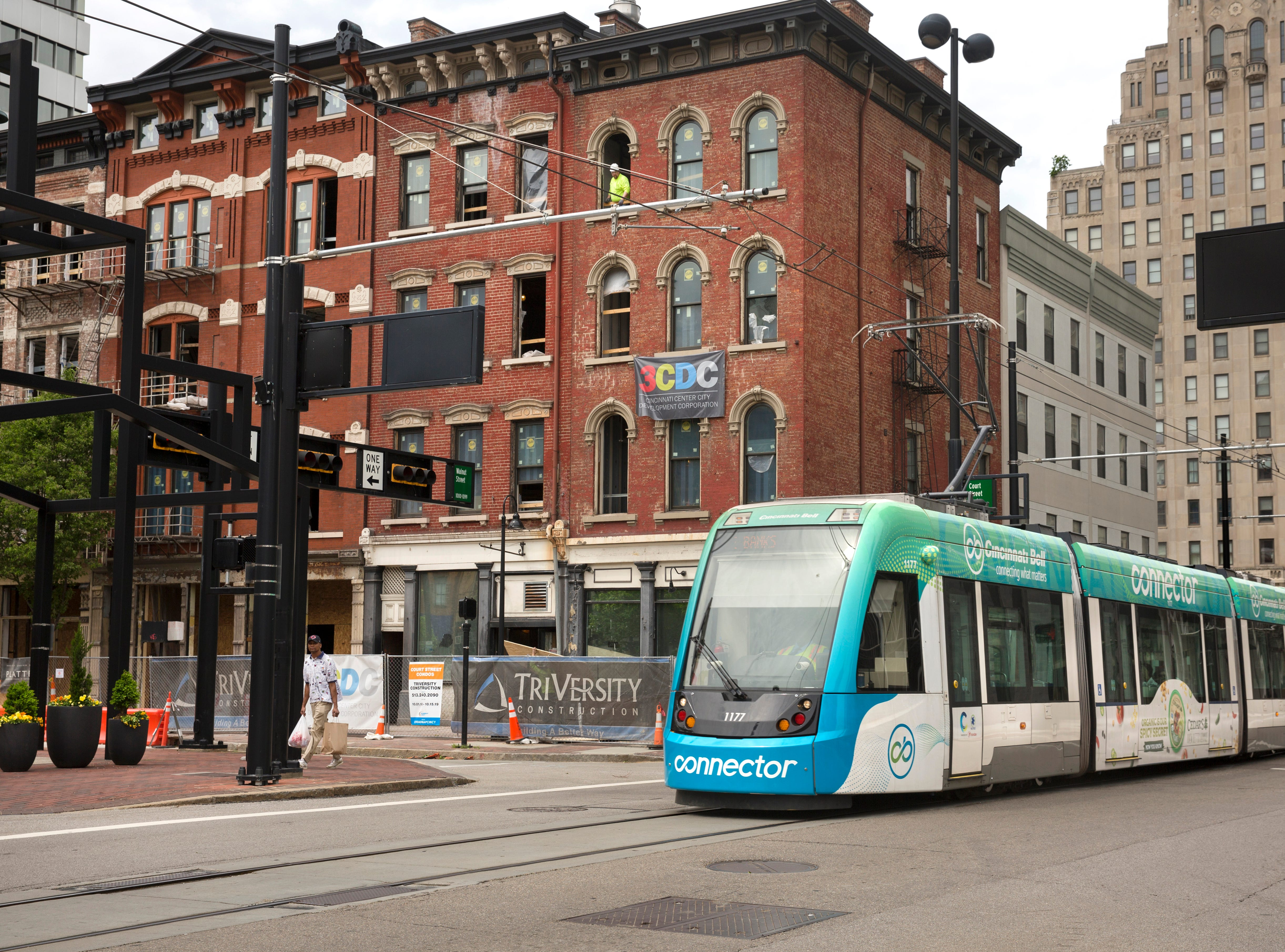 The Cincinnati Bell Connector makes its way down Walnut Street crossing Court Street in downtown Cincinnati, May 1, 2019. At left are the Court Street Condos. It's 3CDC's first residential project south of Central Parkway. The six historic buildings will have 16 condo units with an average price of $313,000. The ground floor will be commercial space. Just down the street at Court and Walnut, Kroger is building a 18-story mixed-use development that includes a grocery story, a 560-space parking garage and 139 apartments.