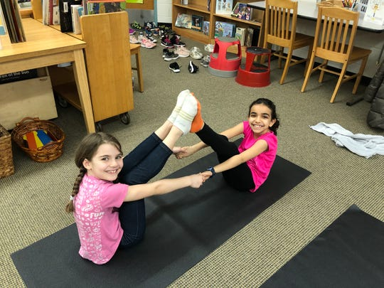 Antigone Kalcanides and Mia Khalil work together during Yoga class.