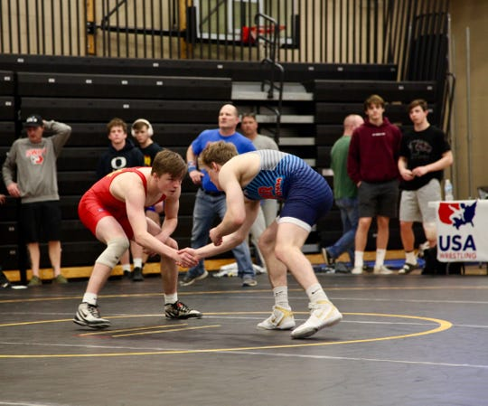 Ankeny's Caleb Rathjen, in the red, wrestles Lisbon's Cael Happel in the finals of the Junior freestyle state tournament at Southeast Polk High School on Saturday, May 4. Happel won, 10-5.