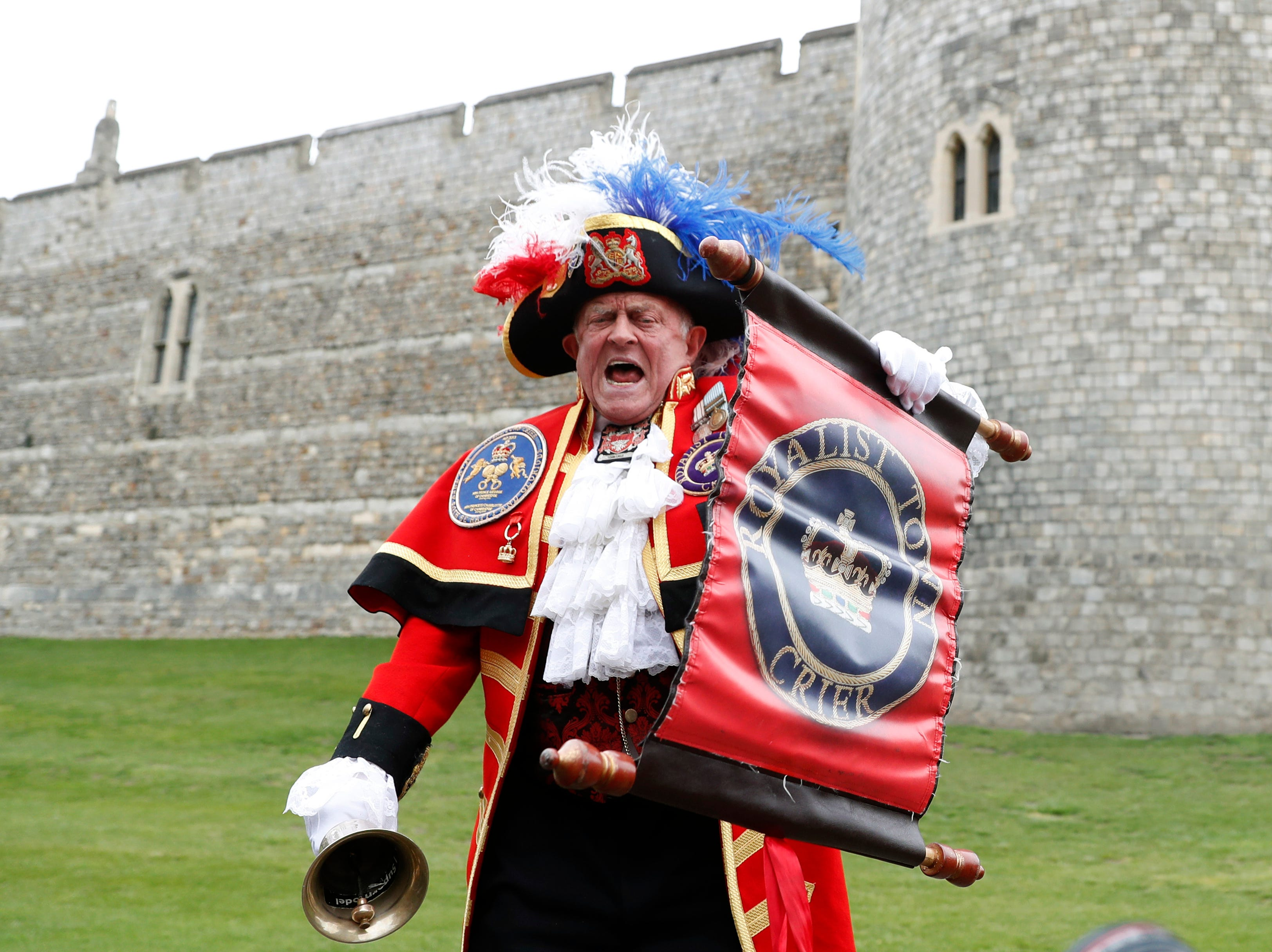 An unofficial Town Crier announces the birth of the baby boy outside Windsor Castle Monday.