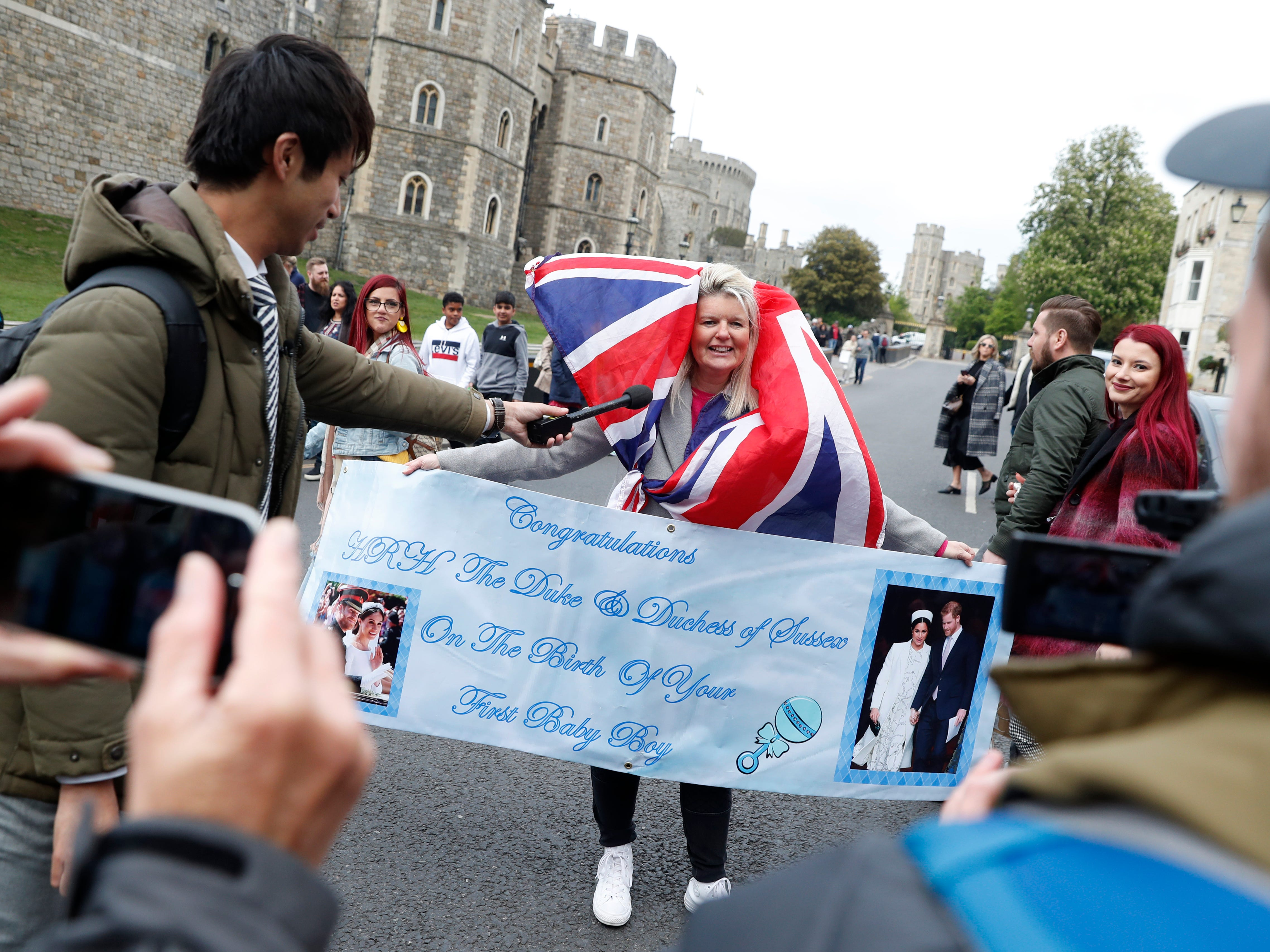 A royals fan carrying a banner is interviewed by a member of the media outside Windsor Castle Monday after the baby's birth was announced.
