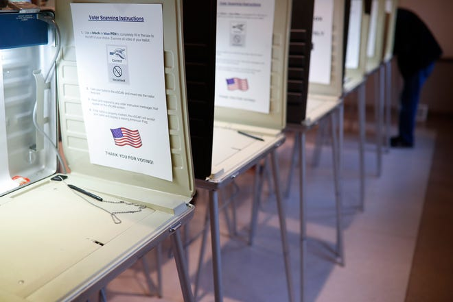 In this Nov. 8, 2016, file photo a lone voter fills out a ballot alongside a row of empty booths at a polling station in the Terrace Park Community Building on Election Day in Cincinnati.