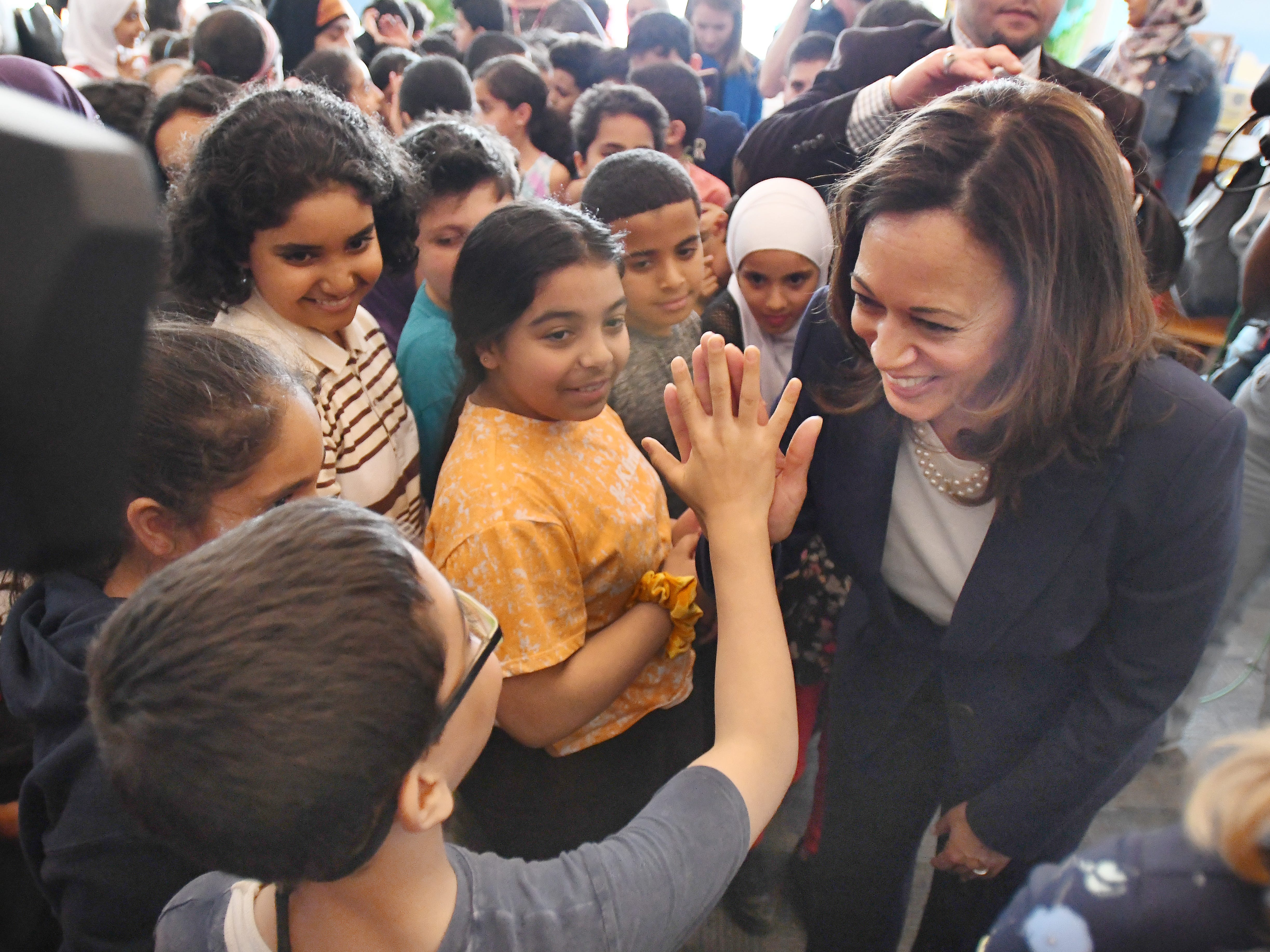 U.S. Senator Kamala Harris 'high-5' a Dearborn 4th grade student at Miller Elementary School after a visit from the Democratic Presidential candidate.