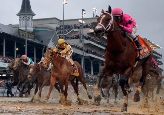 Luis Saez rides Maximum Security, right, across the finish line first against Flavien Prat on Country House during the Kentucky Derby.