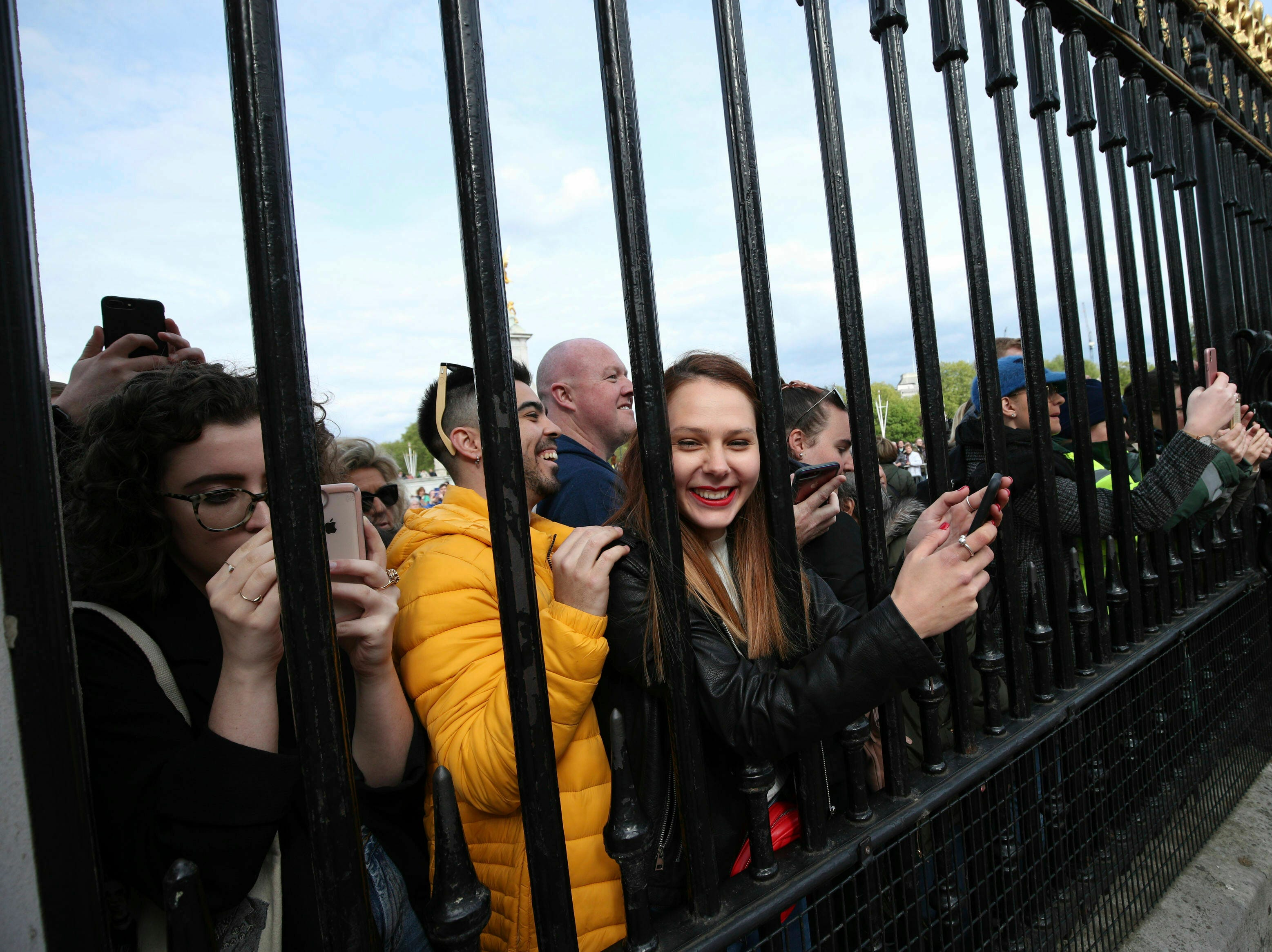 People gather outside Buckingham Palace to take pictures on their mobile phones of the notice placed on an easel to formally announce the royal birth.