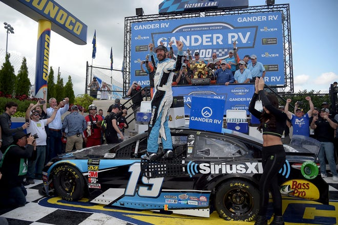 Driver Martin Truex Jr. (19) celebrates in victory lane after winning the NASCAR Cup Series Monday at Dover International Speedway.