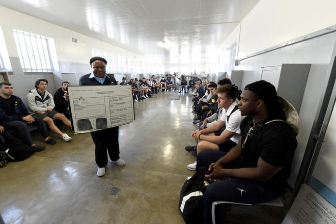 Members of Michigan's football team listen to former prisoner turned guide, Ntando Mbatha, during their visit to Robben Island in Cape Town, South Africa on Sunday.