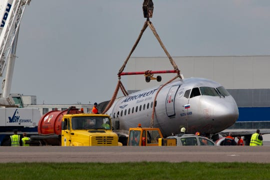 A crane lifts the damaged Sukhoi SSJ100 aircraft of Aeroflot Airlines in Sheremetyevo airport, outside Moscow, Russia, Monday, May 6, 2019.