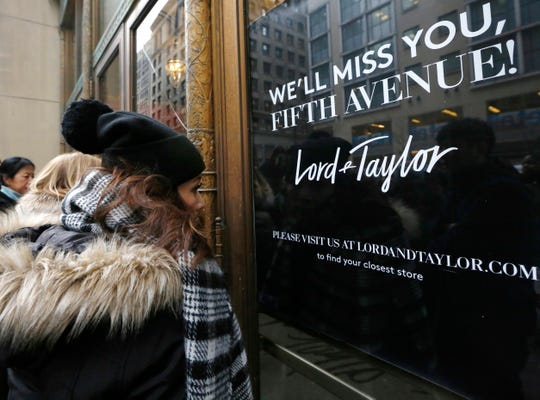 In this Jan. 2, 2019, file photo women peer in the front door of Lord & Taylor's flagship Fifth Avenue store which closed in New York.