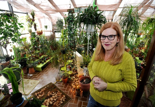 Lisa Steinkopf poses in the sunroom of her own house which she and her husband John  converted into a greenhouse.