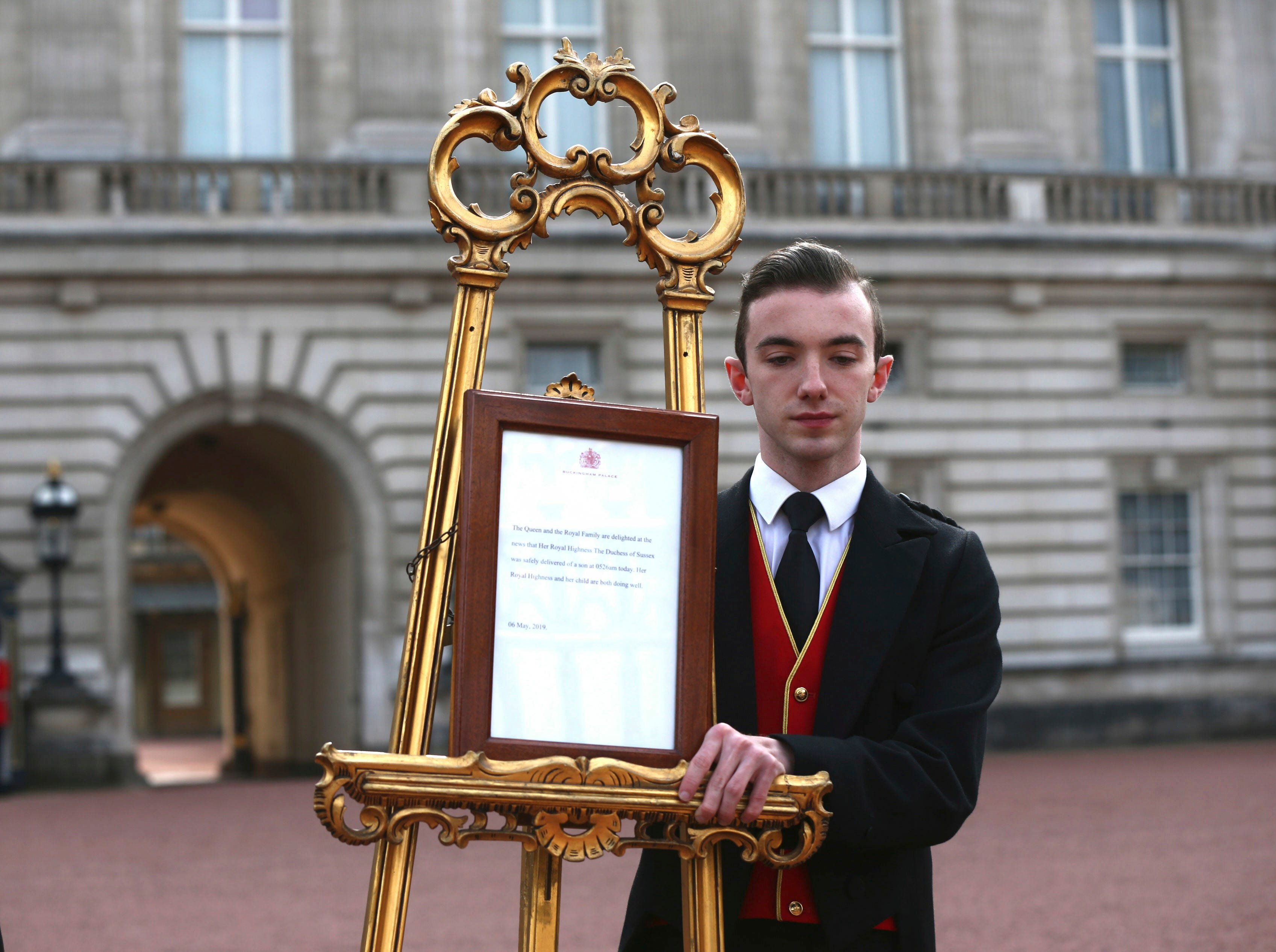 Footmen Stephen Kelly brings out the easel in the forecourt of Buckingham Palace in London to formally announce the birth of the royal baby boy